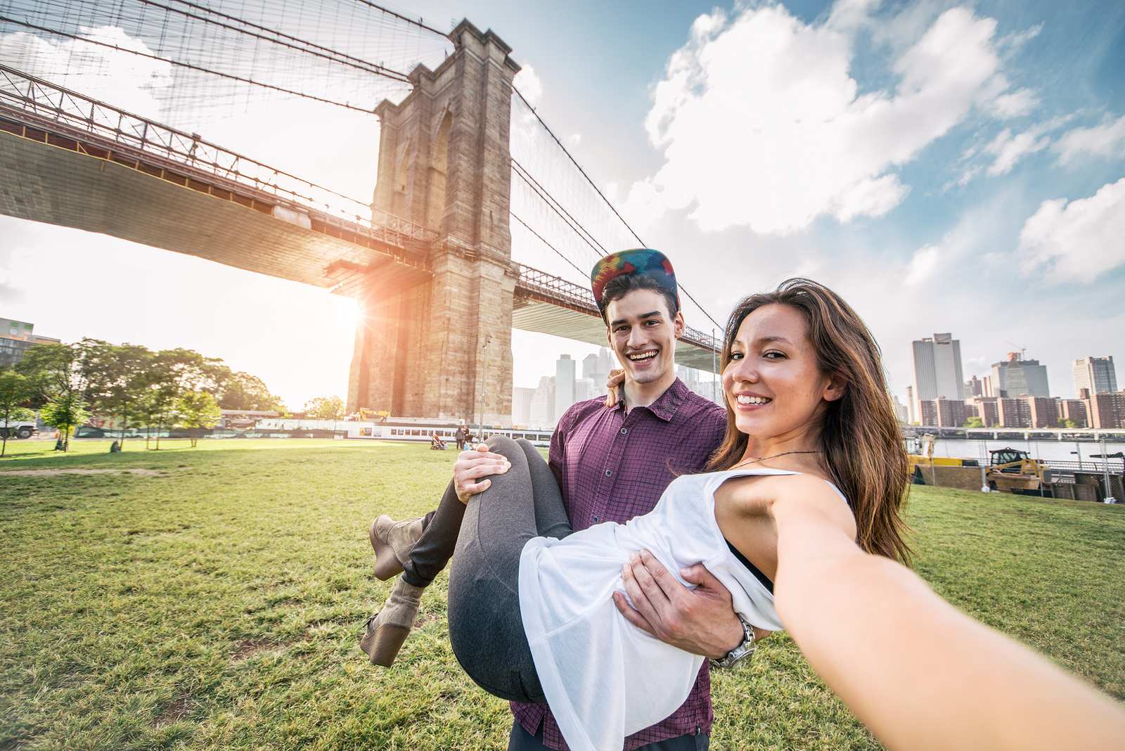 Young pretty couple taking a selfie at Brooklyn Bridge New York - Boyfriend holding his girlfriend and having fun while sightseeing